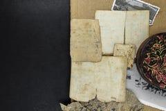 老和年迈的文件的混合,黑背景表面上的照片和金属箱子 免版税库存图片