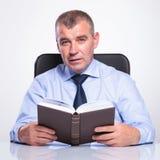 老商人拿着一本书在他的书桌 图库摄影