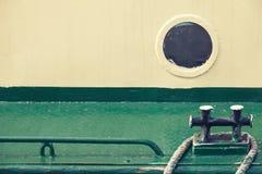 老圆的舷窗和黑停泊系船柱 免版税库存图片