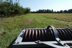 老圆盘耙在领域的边来果树园 库存图片