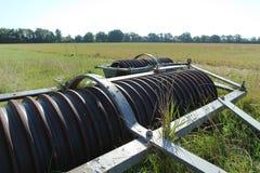 老圆盘耙在领域的边来果树园 免版税库存图片