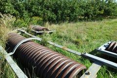 老圆盘耙在领域的边来果树园 图库摄影