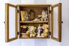 老土气木镶嵌墙上的摆饰橱、项目、玩具和记忆 库存照片