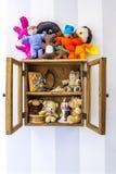 老土气木镶嵌墙上的摆饰橱,项目,充塞了玩具和记忆 免版税库存图片