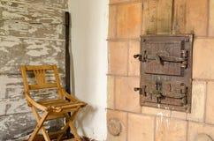 老土气熔炉门和木休息椅子 免版税库存照片