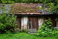 老土气破旧的小棚子在草和森林 免版税库存图片