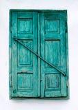 绿色木窗口快门和白色墙壁。 免版税图库摄影