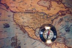 老在古老地图的葡萄酒减速火箭的金黄指南针 选择聚焦 图库摄影