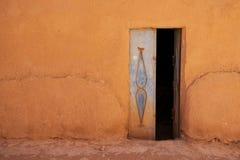 老在地球墙壁的金属蓝色门 黏土和秸杆议院  摩洛哥, tinghir morcco传统房子  小的村庄 免版税库存照片