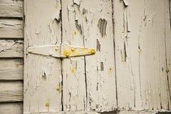 老在木房屋板壁的削皮破裂的白色油漆 免版税库存照片