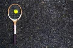 老在被隔绝的石背景的葡萄酒木网球拍与绿色球 图库摄影