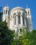 老城堡塔反对蓝天和围拢由绿叶 免版税库存图片