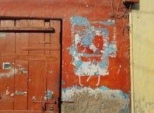 老城市墙壁的抽象背景,贫民窟,红色表面上的一个残破的木门与一张蓝纸的遗骸,在船具 免版税图库摄影