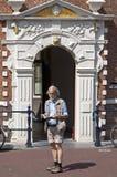 读老城镇厅的荷恩旅行指南的游人 免版税图库摄影