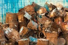 老堆生锈的油漆罐头对墙壁 库存照片