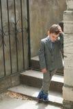 老墙壁和台阶的背景的哀伤的小男孩有门的 免版税库存照片