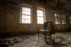 老外套和椅子在一个被放弃的大厦 库存图片