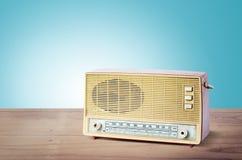 老多灰尘的收音机从1970年在木桌上有蓝色背景 库存图片