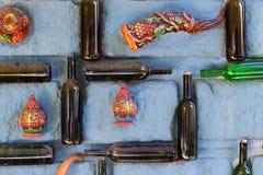 老多灰尘的空的瓶酒,在希腊样式的葡萄酒装饰元素-盘和垫铁喝的在石墙上被胶合 免版税库存照片