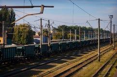 老多灰尘的铁路的看法与运货车和输电线的 库存图片