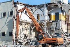老大厦的爆破与挖掘机的 免版税库存照片