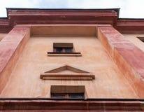 老大厦的特写镜头零件与小窗口的 低角度射击 免版税库存照片