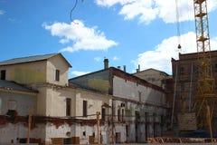 老大厦的破坏,重建,结构变化 建筑,在站点的高层起重机工作 的treadled 免版税库存图片