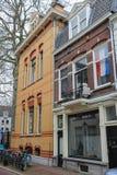 老大厦门面与国旗的在窗口后在Utrec 库存照片