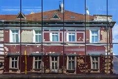 老大厦门面在现代旅馆窗口里反射了  图库摄影