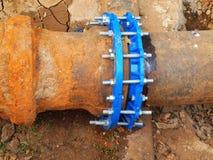 老大饮料水管加入与新的蓝色阀门和新的蓝色联合成员 完成的被修理的管道系统等待的覆盖物  免版税库存照片