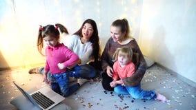 老妇人与使用膝上型计算机的女孩孩子和姐妹一起花费时间和坐在背景的地板 股票录像