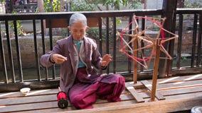 老妇人做织品生产的螺纹 免版税库存照片