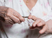 老妇人切制钉在家 免版税库存图片