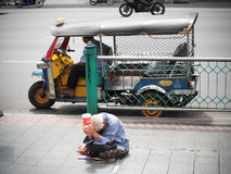 老妇人叫化子乞求为在边路的捐赠在城市 免版税库存图片
