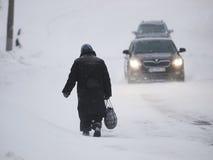老妇人和汽车在被雪包围住的路 库存照片