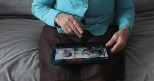老妇人和电子片剂的手 股票录像