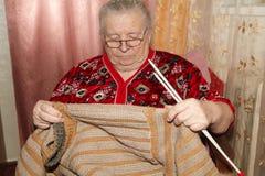老妇人和编织的毛线衣 免版税库存图片