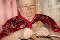 老妇人和编织的毛线衣 免版税库存照片