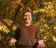 老妇人在五颜六色的叶子背景的耸肩肩膀  库存图片