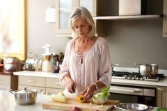 老妇人在准备健康膳食的厨房里 免版税库存图片