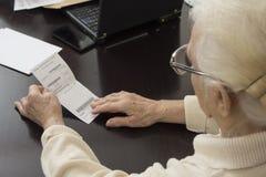 老妇人在她的手上举行一张处方并且读 免版税库存照片