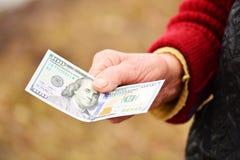 老妇人在她的手上拿着金钱 金钱在老妇人手上 免版税库存照片