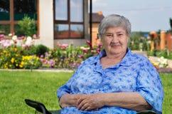 老妇人在庭院里 库存图片