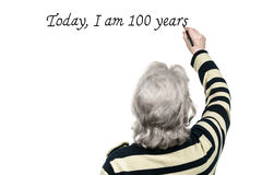 老妇人在有标志的墙壁写 免版税库存图片