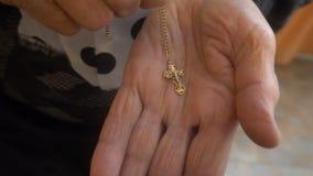 老妇人在棕榈上把基督徒十字架放 影视素材