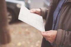 老妇人在街道的读书地图 库存照片