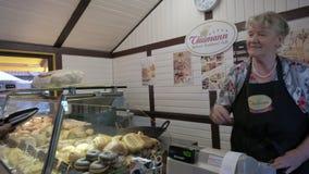 老妇人在面包店商店愉快地为顾客[平的外形服务] 股票录像