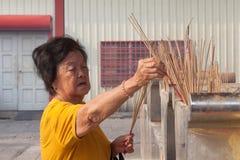 老妇人在Kuan尹寺庙,槟榔岛烧香火 免版税库存照片