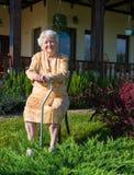 老妇人坐与藤茎的一把椅子 免版税库存照片
