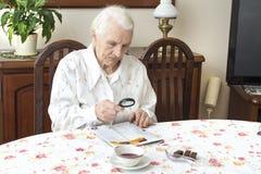 老妇人坐在与报纸的一张桌上 免版税库存图片